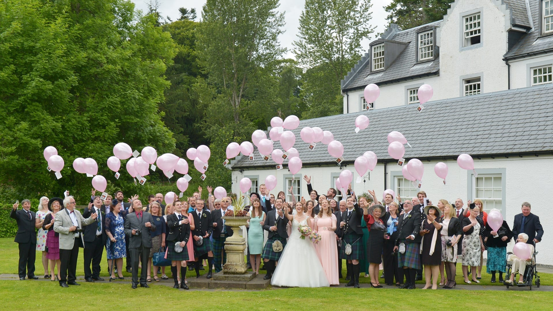 Wedding guests release balloons at Barony Castle