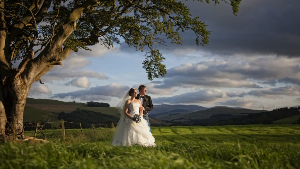 Bride and groom with backdrop of hills behind at Barony Castle